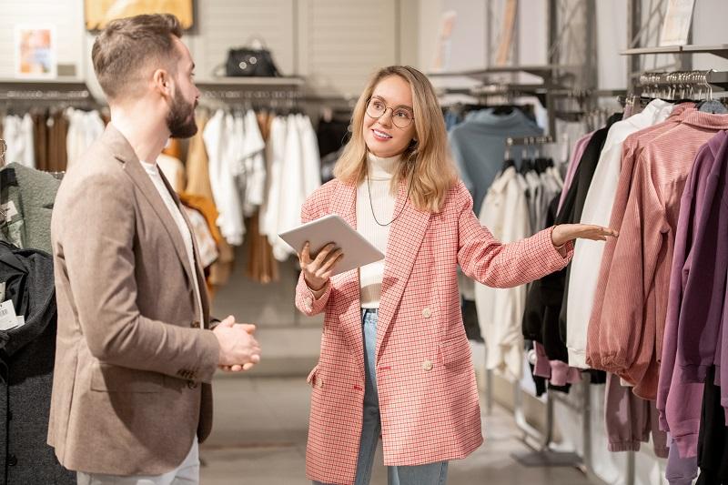 sprzedawczyni w sklepie odzieżowym obsługuje klienta